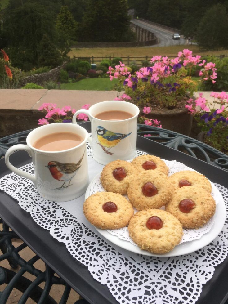A plate of Melting Moments biscuits ready to enjoy, sitting on a table in the garden with two mugs of proper Yorkshire tea