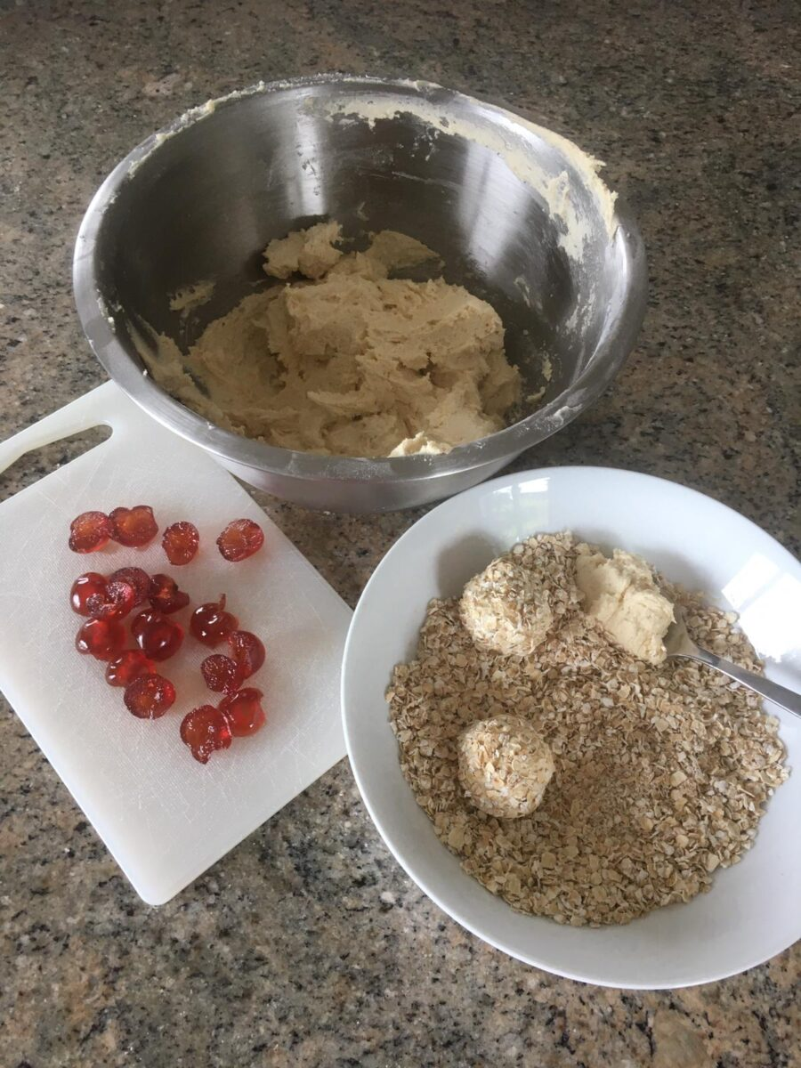 Spoonfuls of batter are dropped into the bowl of oats and rolled into balls before they go on the baking tray. We can see the halved glace cherries on a chopping board, ready to be added when the balls are on the tray.
