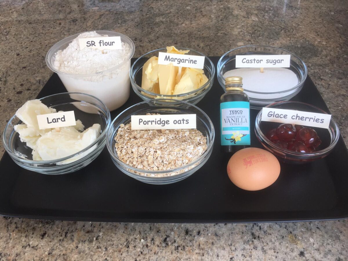 All the ingredients you need to make Melting Moments biscuits, weighed out ready for use: caster sugar, margarine, shortening/lard, porridge oats, 1 large eggs, glace cherries and vanilla essence
