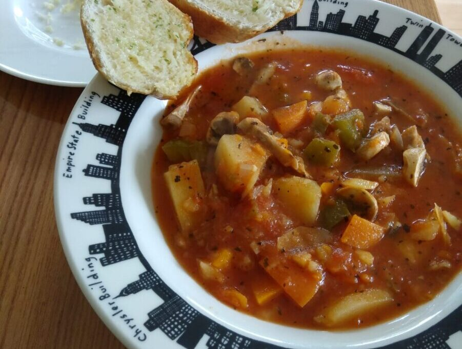 A bowl of simple soup served with two slices of garlic bread. Chunks of potato, carrot and green pepper can be seen against a tomatoey liquid base.