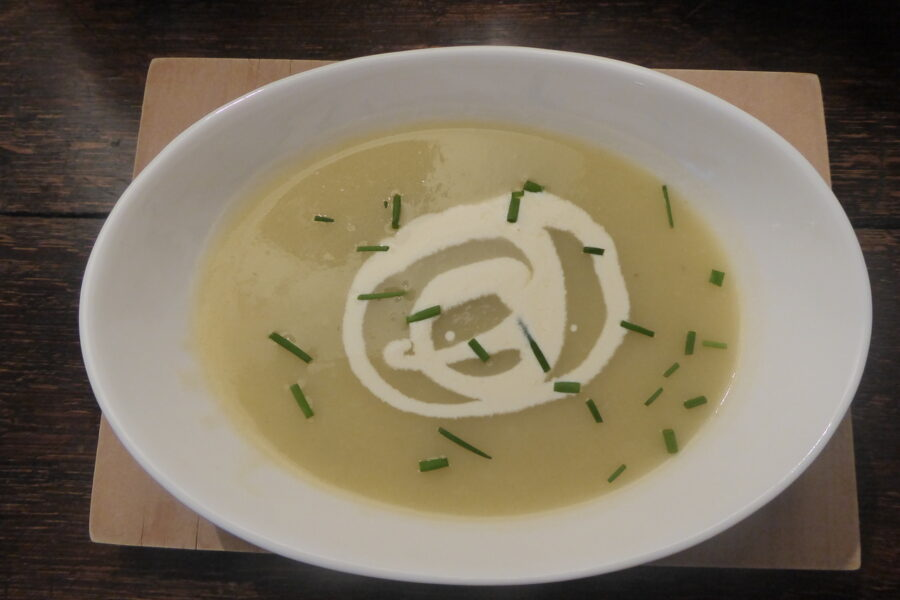 A bowl of leek and potato soup garnished with a swirl of cream and some chopped chives