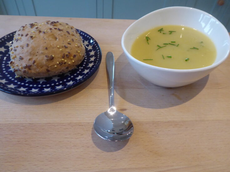 A seeded roll on a plate, next to a bowl of pale green leek and potato soup that has chopped chives scattered on top, and a spoon placed ready to tuck in
