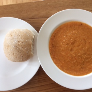 A bowl of tomato, courgette and pepper soup next to a plate with a crusty roll