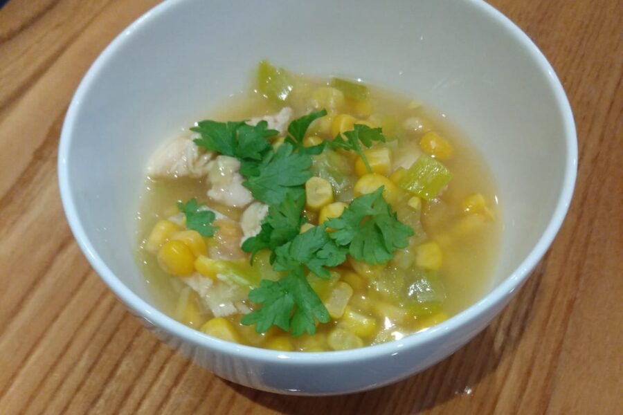 A bowl of chicken leftover soup, garnished with chopped fresh herbs