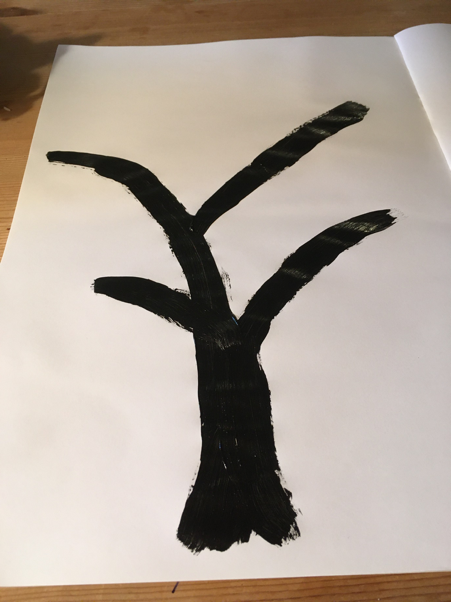 A tree trunk and branches painted in brown on a piece of paper