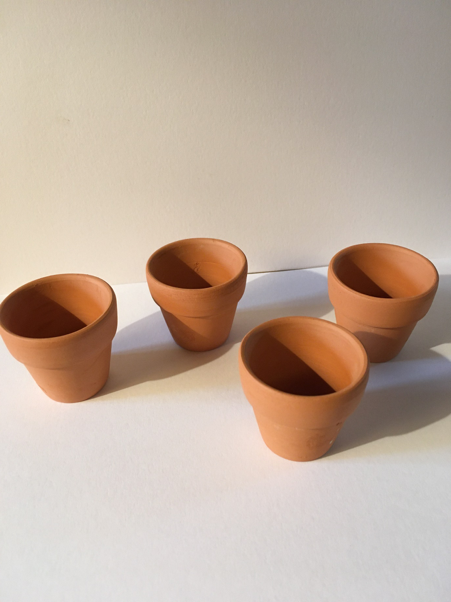 Four small terracotta plant pots waiting for use