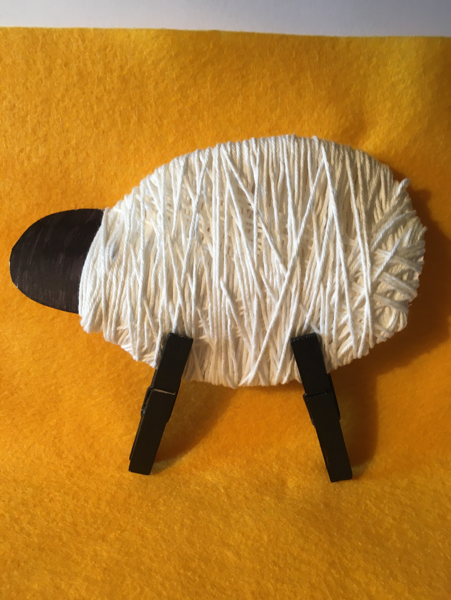 Clip the painted clothes pegs to the bottom of the wrapped card tp make the sheep's legs