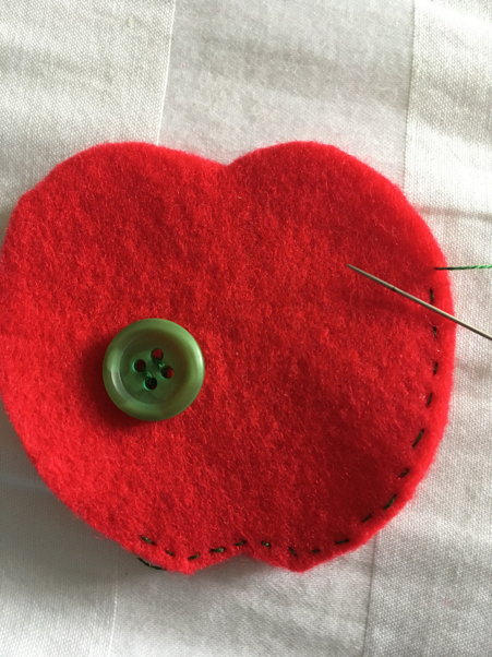 Thread the needle with green cotton and start to sew around the edge