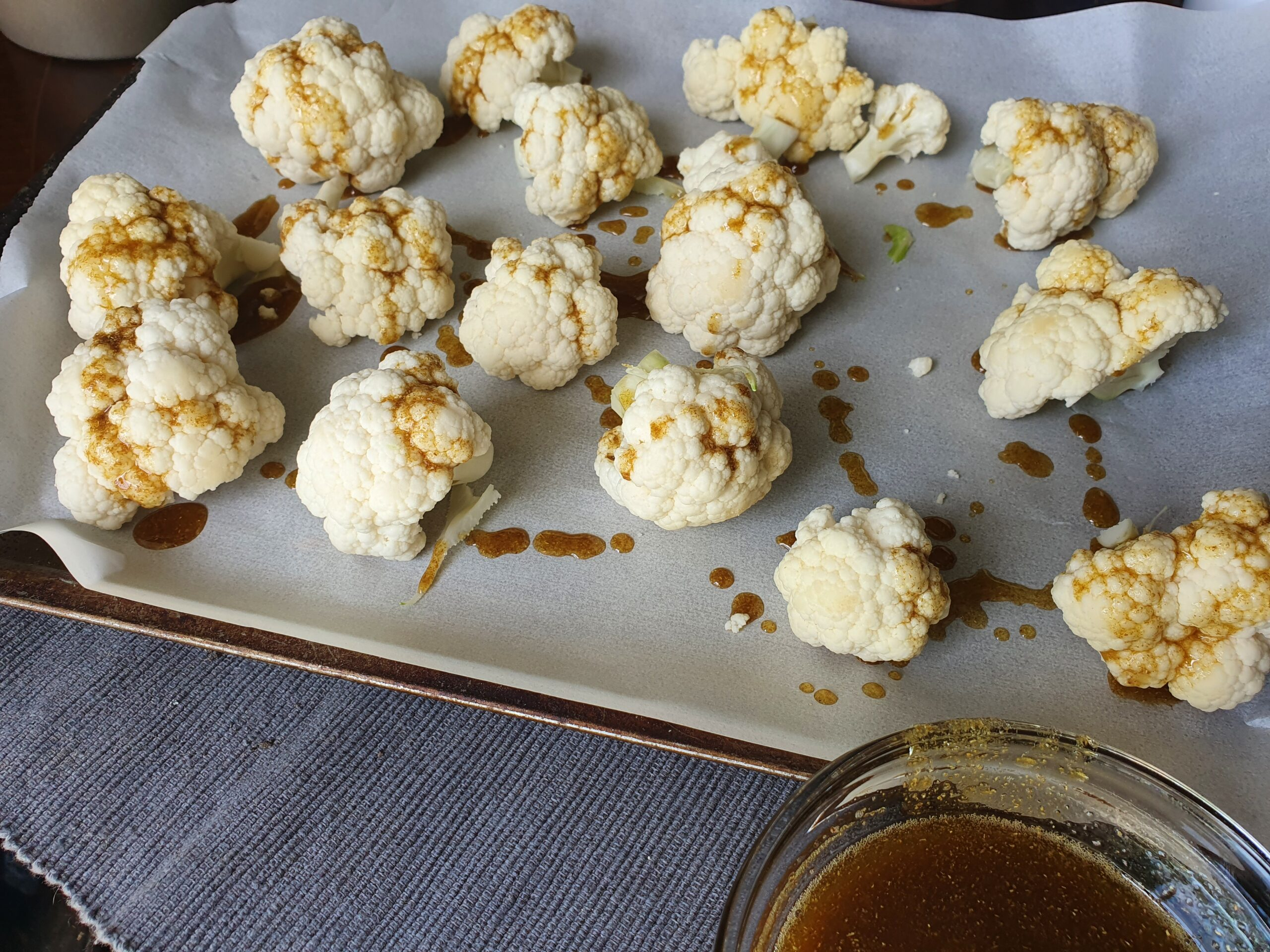 The cauliflower on the baking sheet has been sprinkled with the spice and olive oil mixture