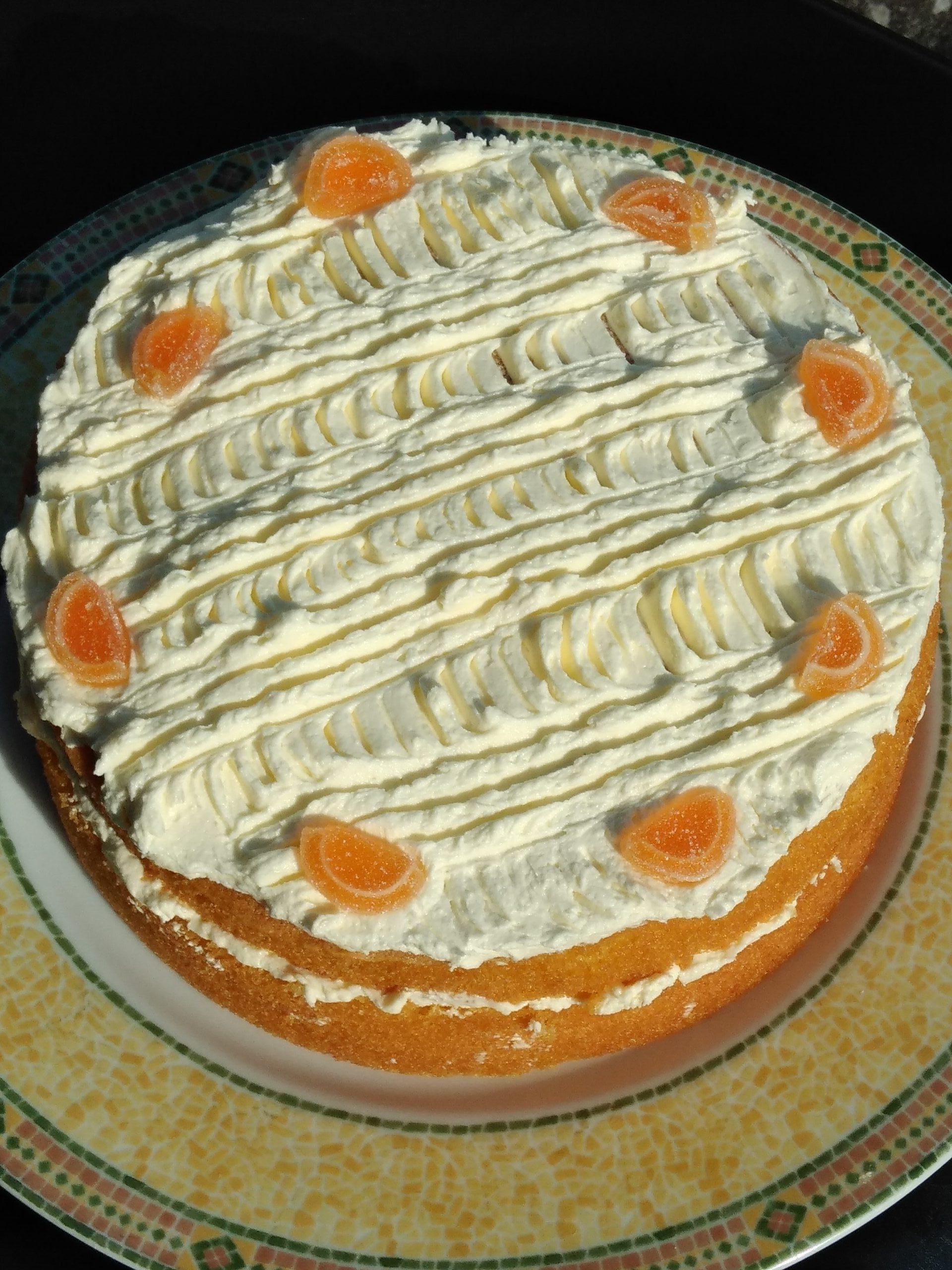 The orange cake has been decorated with jelly orange segments on top of the buttercream