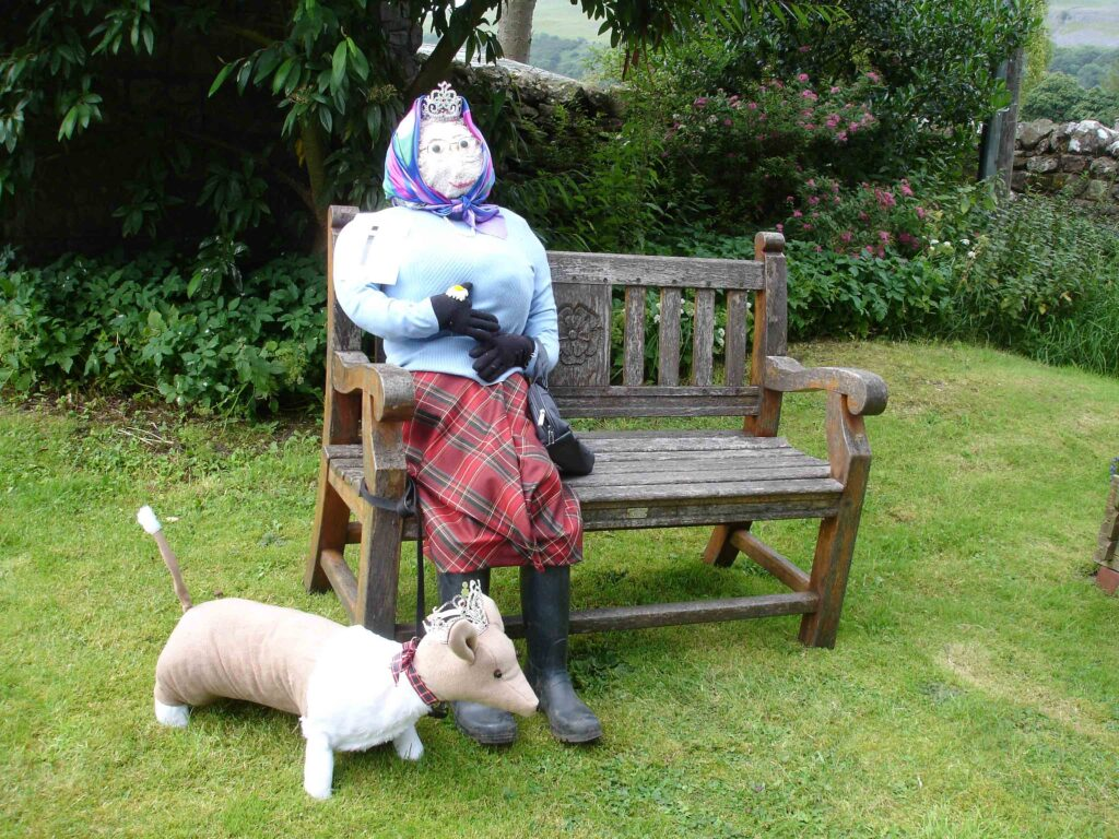 A female scarecrow on a bench, wearing a headscarf, and with a small, honey-coloured dog at her feet. She's wearing a tiara: I wonder if she's royalty?