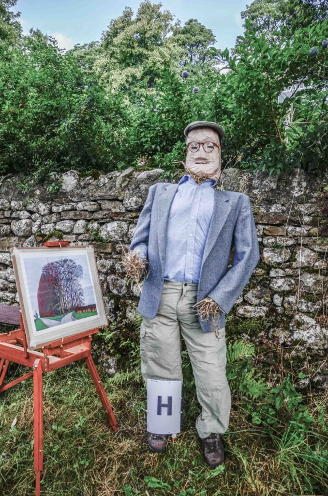 A scarecrow artist stands next to an easel. Is that a swimming pool he's painting?