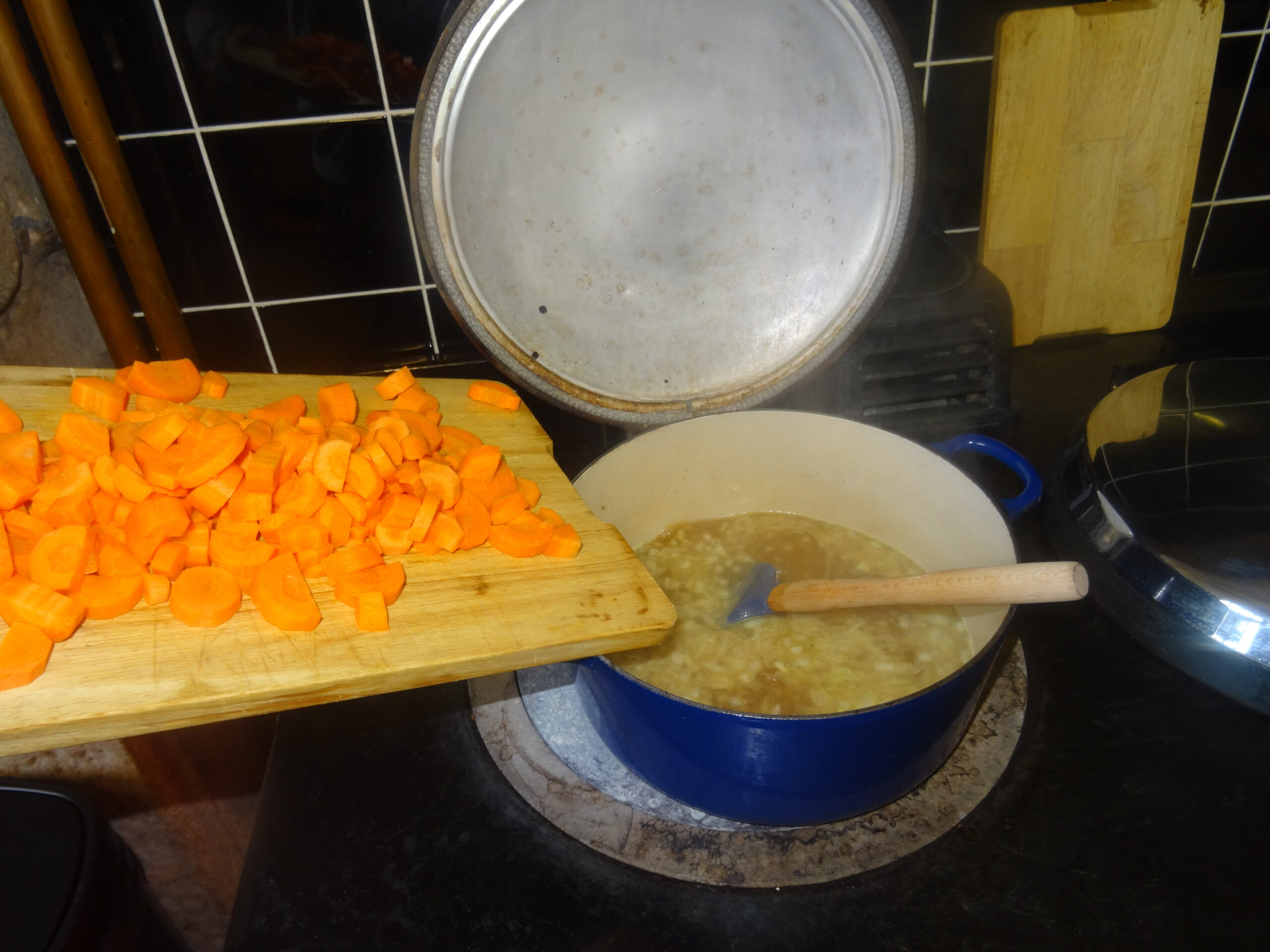 Adding the chopped carrots to the pan of stock and onions