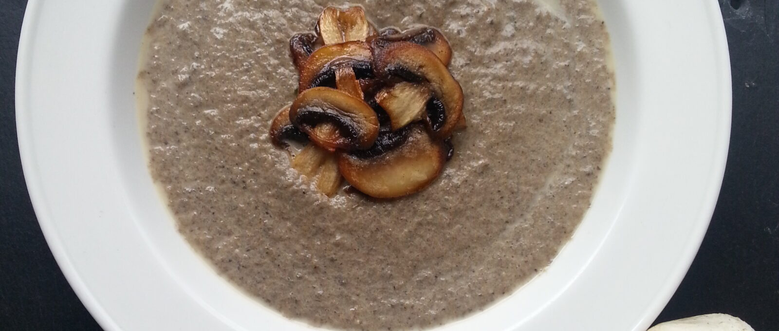 A bowl of delicious mushroom and roast garlic soup, garnished with fried slices of mushroom