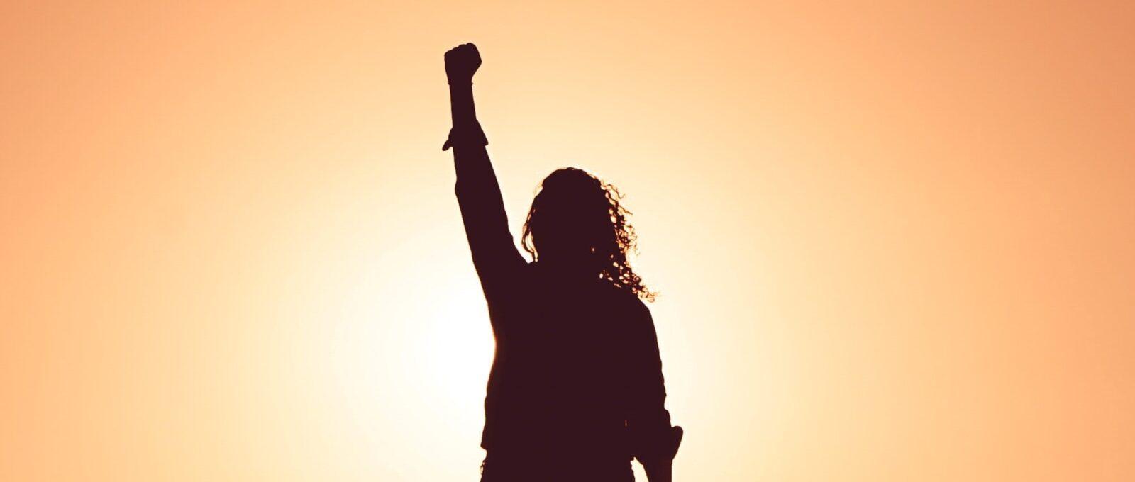 Person raising hand aloft against a sunset
