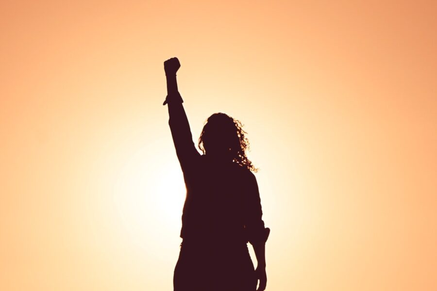 Person raising hand aloft against a sunset