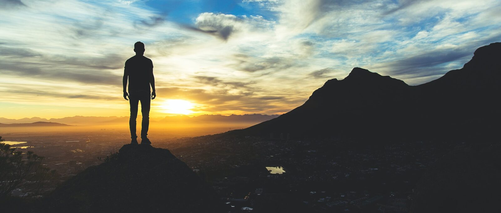 Silhouette of a man against a sunset sky