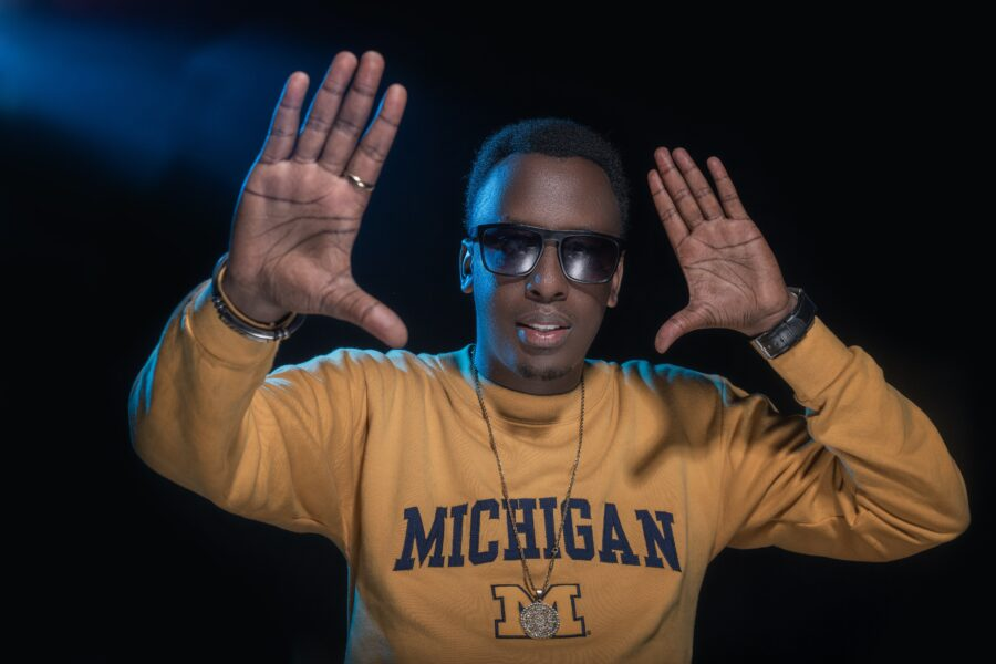 A man in a sweatshirt with Michigan written across the front, dancing to the song Rhythm of Life.
