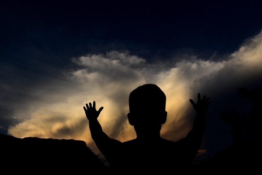 A man silhouetted against a night sky, raising his hand in praise