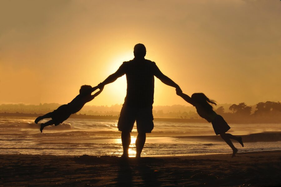 A man on a beach, silhouetted against the sea and the sunset sky, swinging a child from either hand